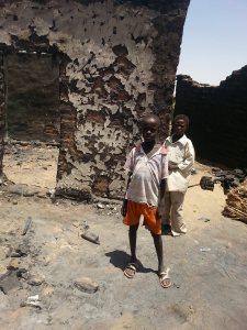Six, burnt village, Kenjara area, with people examining, April-May 2014